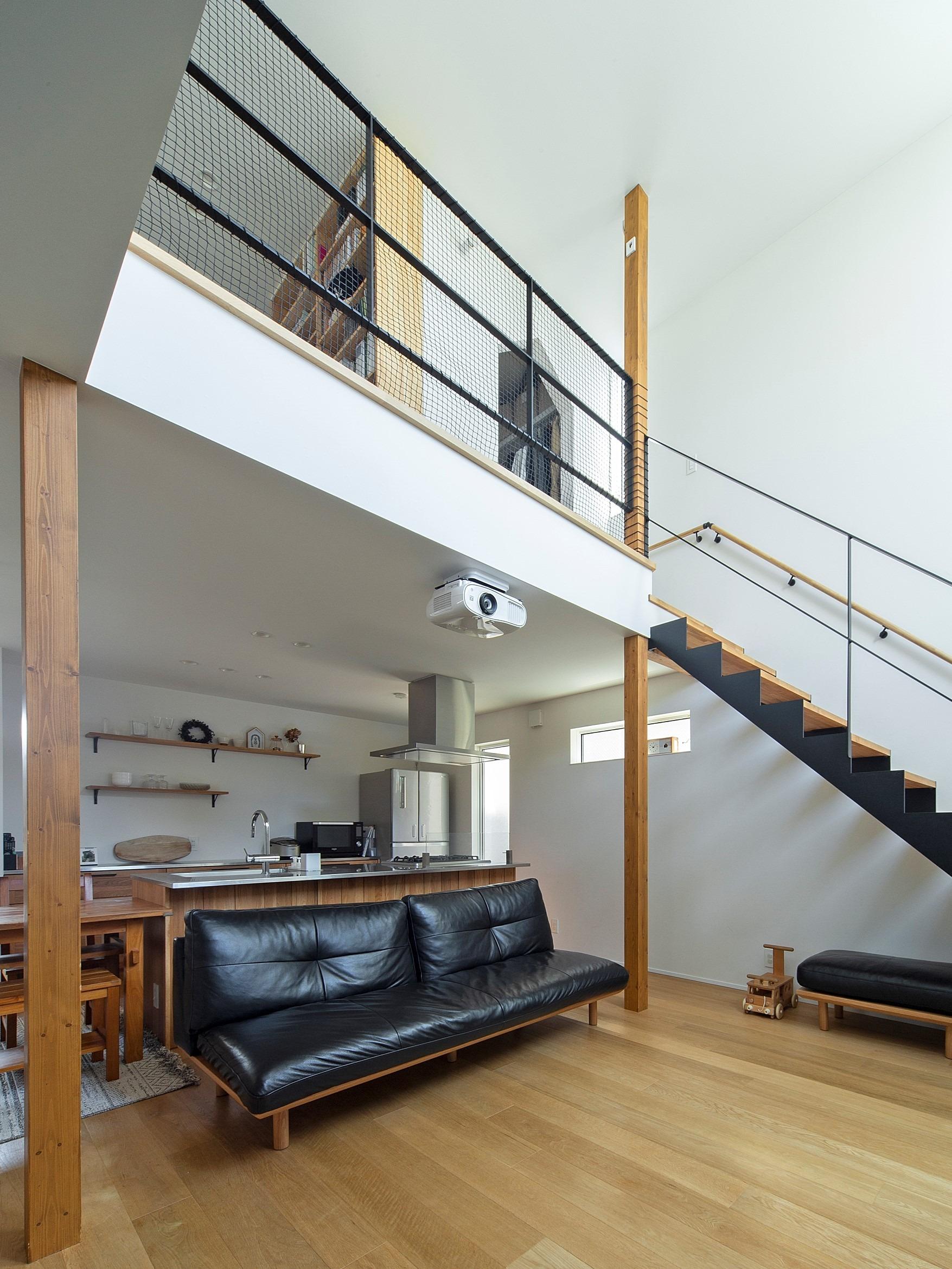 鉄骨階段で空間をつなぐ。ホワイトの漆喰でできた、大きな壁に映えるブラックの鉄骨階段